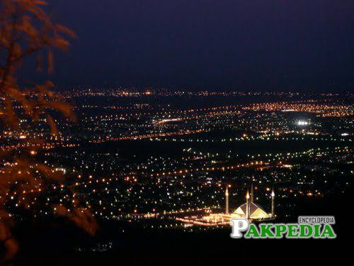 A scenic view of the city from the Margalla Hills at night