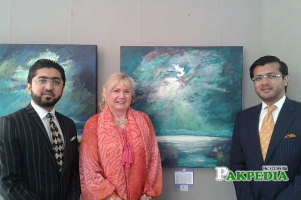Hasnain is standing beside Sandra and Ali is on the other side of his Painting