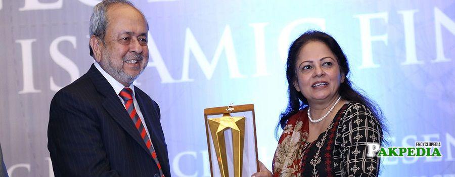 Aisha Ghaus presenting an award to Dr Junaid Zaidi