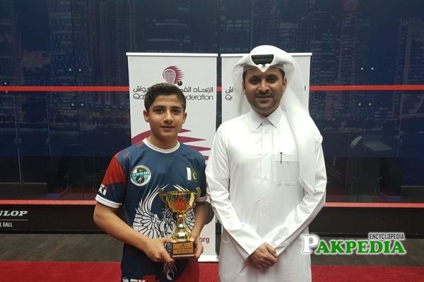 Champion of Squash Hamza Khan holding his trophy