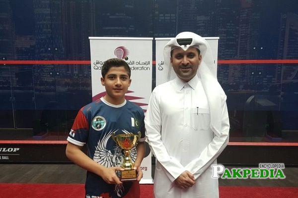 Champion of Squash Hamza Khan holding his trophy