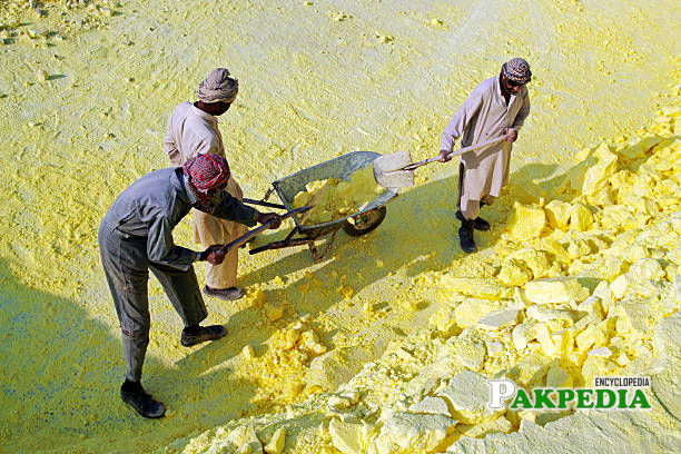 Workers collect sulphur at the Dakhni Gas Processing Plant, operated by Oil & Gas Development