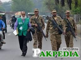Pakistani soldiers walk with an official (L) from the Pakistan Bureau of Statistics