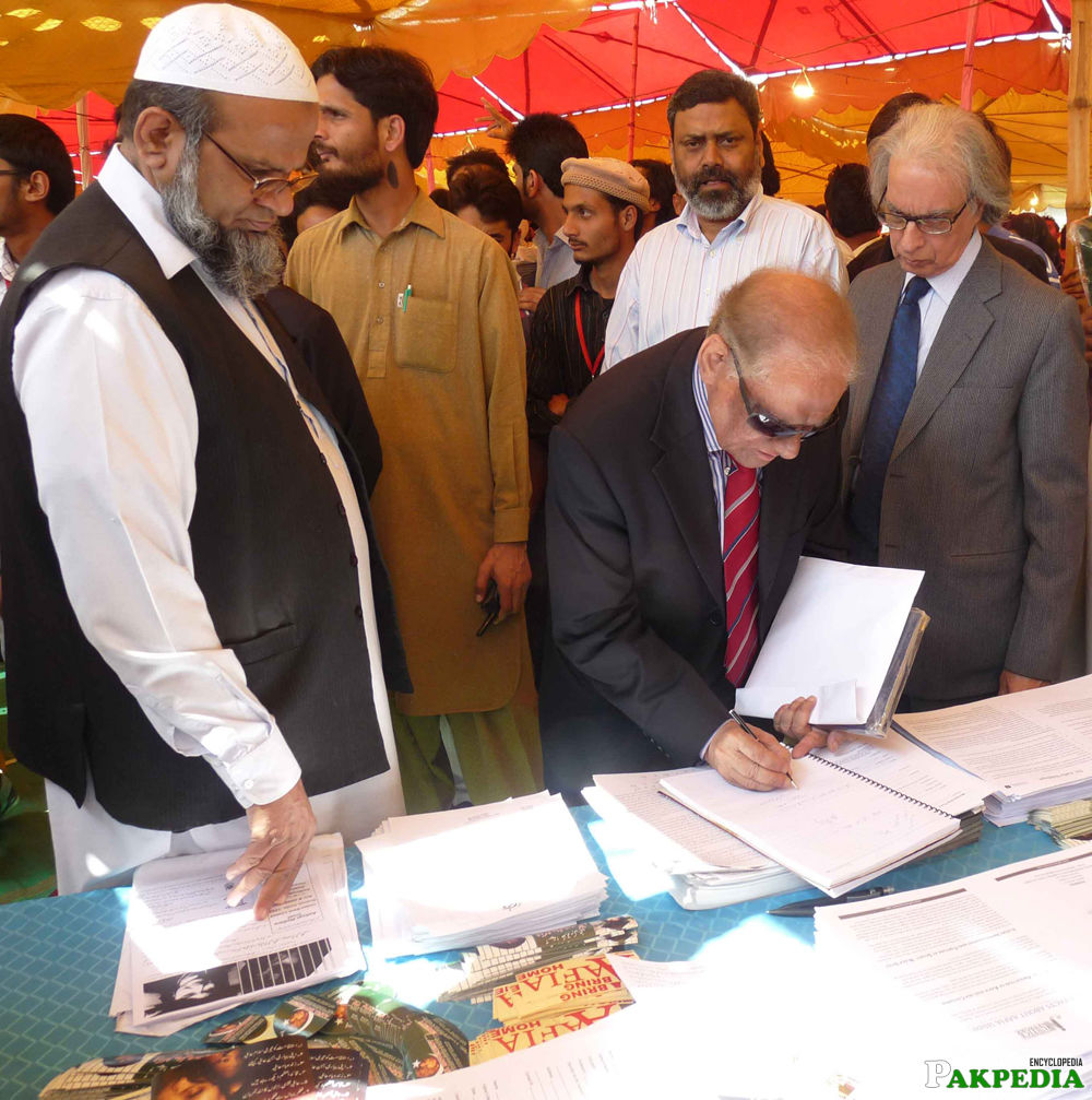 Saeeduzzaman Siddiqui is checking ang singing the documents