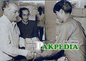 Rahman receiving the first prize from Faiz Ahmad Faiz