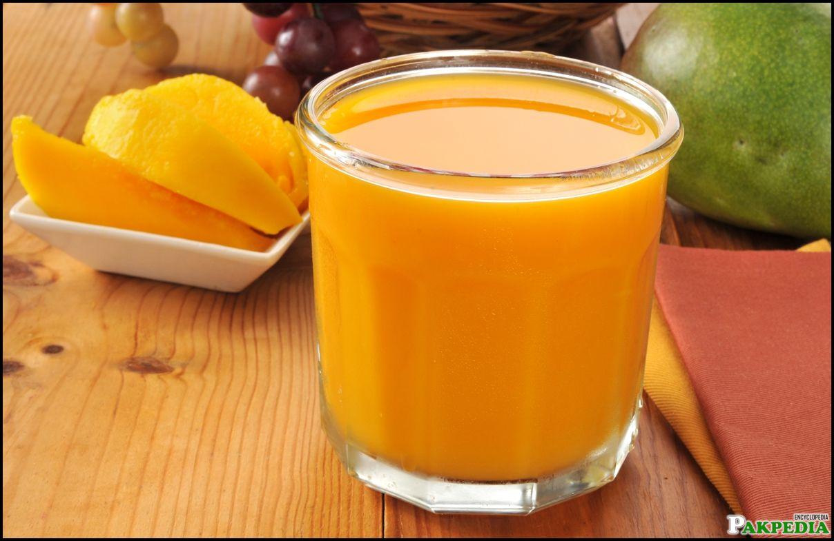 A glass of fresh mango juice with a bowl of sliced mango